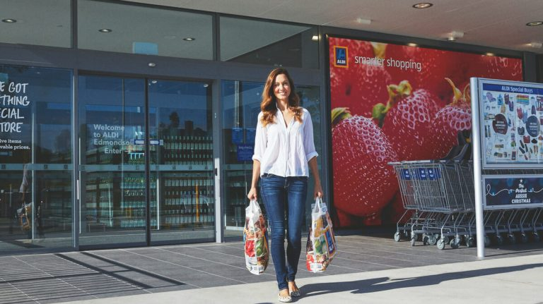 a lady coming out of aldi market after shopping